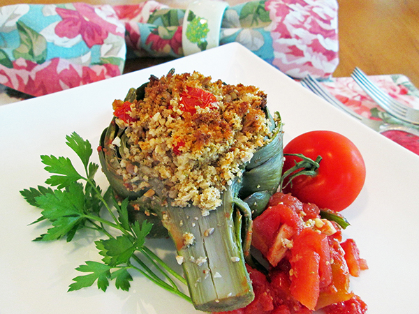 stuffed artichoke on plate with tomato