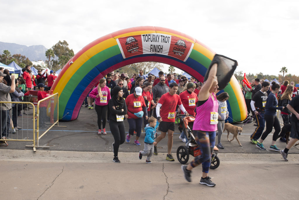 Racers cross the finish line, an inflatable rainbow arch, at a Tofurky Trot